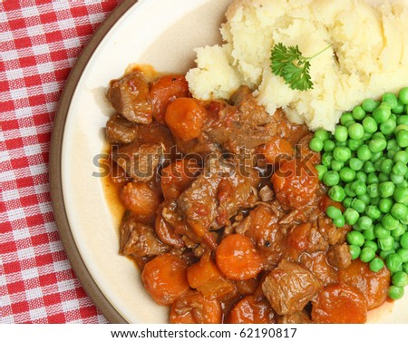 Beef stew with mashed potato and peas. - stock photo