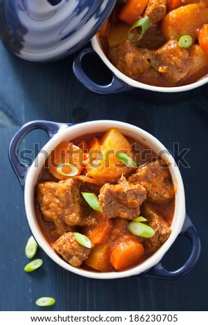 beef stew with potato and carrot in blue pots  - stock photo