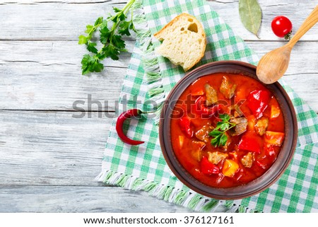 Beef stew with potato, sweet pepper, onion, carrot, tomatoes and spices, traditional hungarian soup decorated with parsley, closeup, top view - stock photo