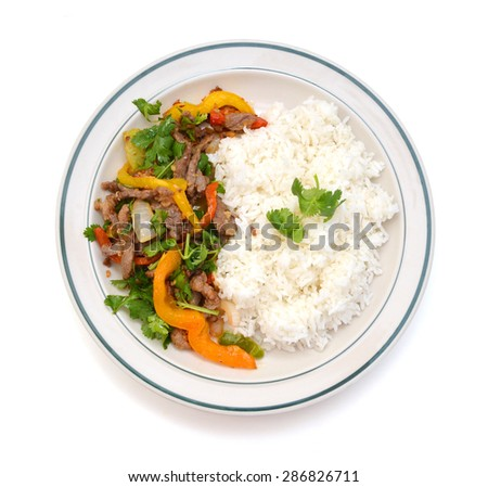 beef stir fry over white rice. in white plate on white  - stock photo