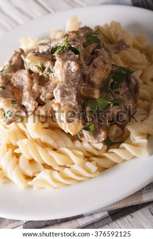 beef stroganoff with pasta fusilli closeup on a plate on the table. vertical
