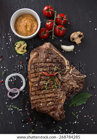 Beef t-bone steak on black stone table, close-up. - stock photo