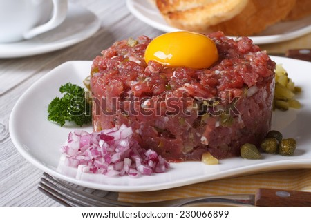 beef tartare with egg and vegetables closeup on a white plate. horizontal  - stock photo