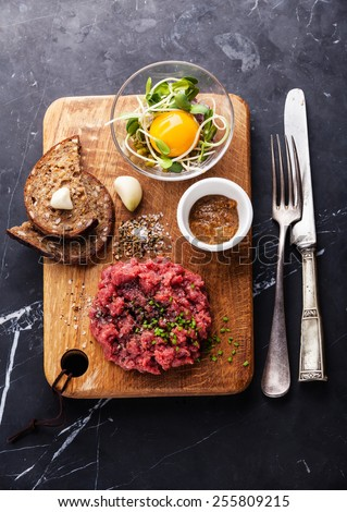 Beef tartare with salad and garlic toasts on dark marble background - stock photo