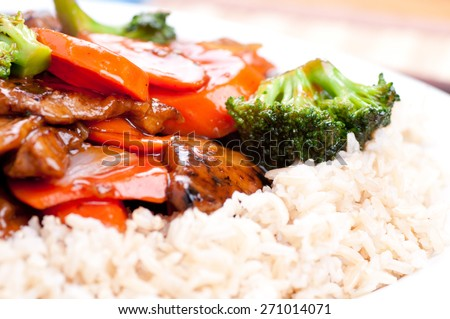 beef with broccoli and carrot stir fry over brown rice - stock photo