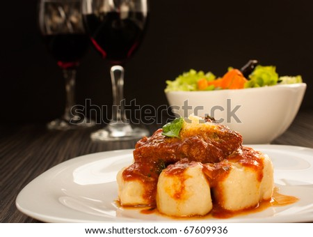 Beef with sauce,  gnocchi and salad. - stock photo