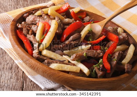 Beef with vegetables and fries - Lomo saltado close-up on a plate. Horizontal, rustic