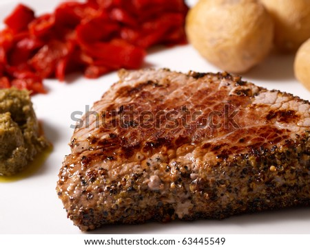 Beefsteak with pepper crust served with garnish and sauce - stock photo