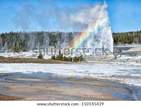Beehive Geyser Eruption with Rainbow - stock photo