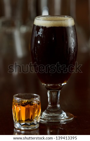 beer and a shot of whiskey served on a busy out of focus bar - stock photo