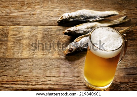 beer and fish vobla on a dark wood background. tinting. selective focus on beer - stock photo