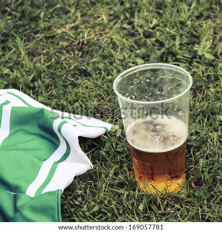 Beer and football dress on grass - stock photo