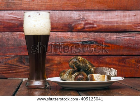 beer and grill sausage  on wooden background - stock photo