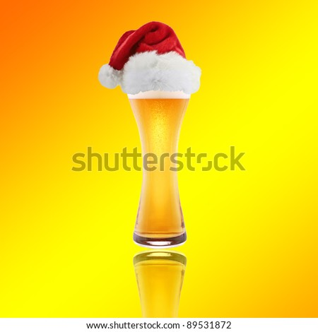 Beer and hat of Santa Claus on a yellow background - stock photo