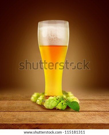 beer and hop in glass of light on planking dark abstract background