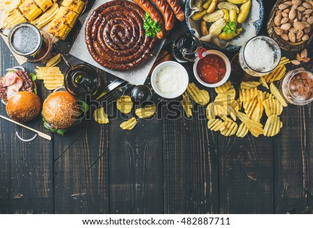 Beer and snack set. Oktoberfest food frame concept. Variety of beers, grilled sausages, burgers, corn, fried potatoes, chips, salted almonds and sauces on dark wooden background. Top view, copy space