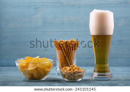 Beer and snacks, chips, bread sticks and peanuts - stock photo
