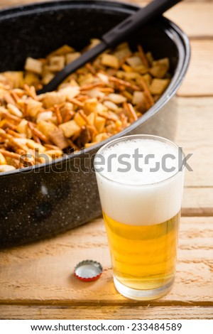 Beer and Snacks - This is a shot of a cold beer sitting on a wooden table next to a holiday party food mix. Shot with a shallow depth of field. - stock photo