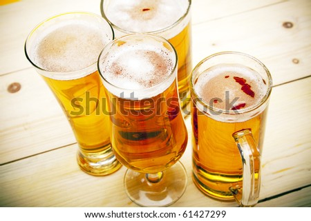 Beer and wheat on wooden flood! - stock photo