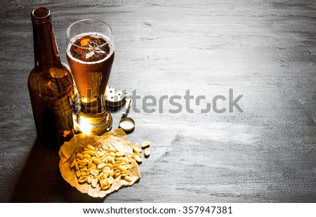 Beer background. Beer with peanuts on the black wooden table. Free space for text. - stock photo