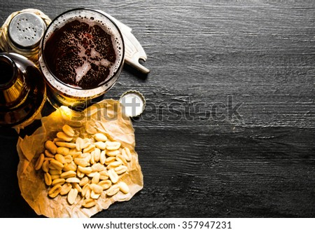 Beer background. Beer with peanuts on the black wooden table. Free space for text. Top view - stock photo