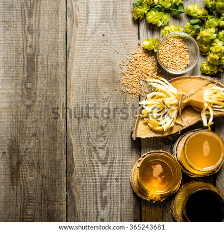 Beer background. Fresh beer and the salty cheese on a wooden table. Top view - stock photo