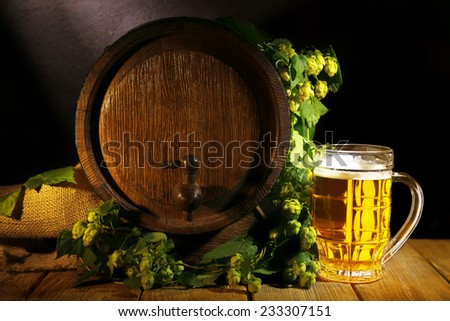 Beer barrel with beer glass on table on wooden background - stock photo