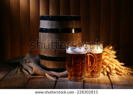 Beer barrel with beer glasses on table on wooden background - stock photo