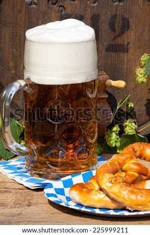 Beer barrel with hops, a large glass of beer and a pretzel on a paper plate