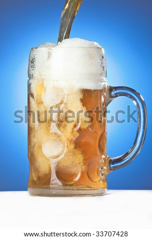 Beer being drawn into an Oktoberfest Mass Glass on a blue background.