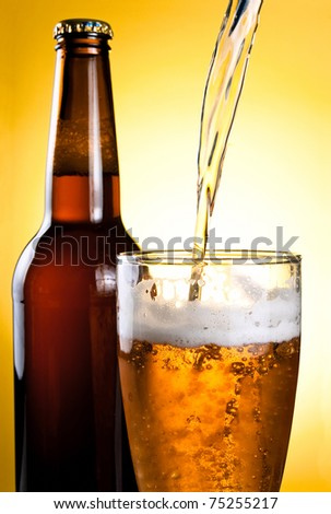 Beer Being Poured in Glass and Bottle on yellow background - stock photo