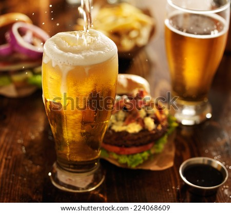 beer being poured into glass with gourmet hamburgers - stock photo