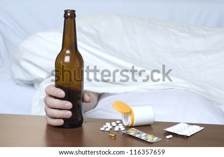 Beer Bottle and various drugs on the table. On the right space for text and graphics. - stock photo