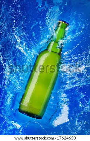 beer bottle being poured in a water - stock photo