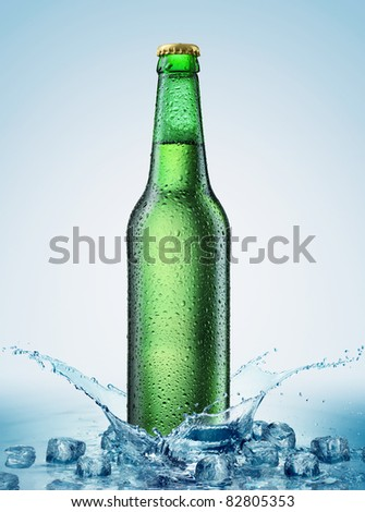 beer bottle being poured in a water with ice - stock photo