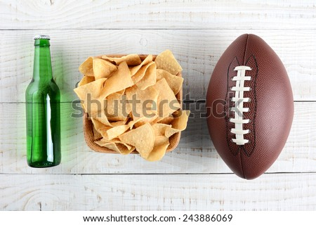 Beer bottle, bowl of chips and an American style football on a rustic whitewashed wood surface. Horizontal format. The bottle is without label. - stock photo