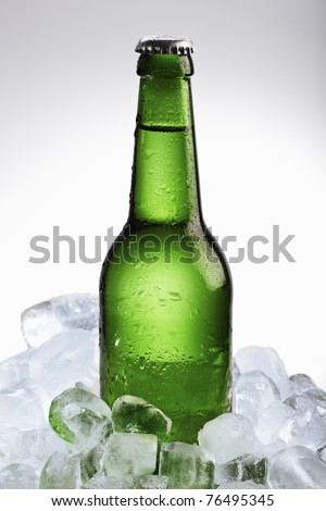 Beer bottle in ice cubes over white background - stock photo