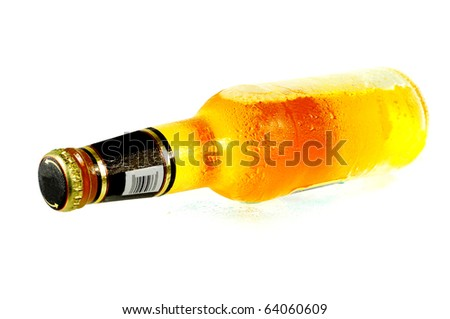 Beer bottle laying on a glass surface isolated on white - stock photo
