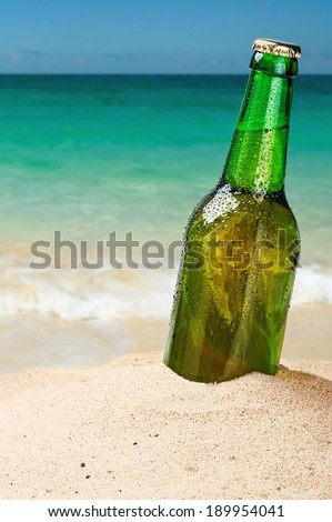 Beer bottle on a sandy beach with clear sky - stock photo