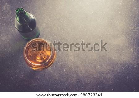 Beer bottle on dark table - stock photo