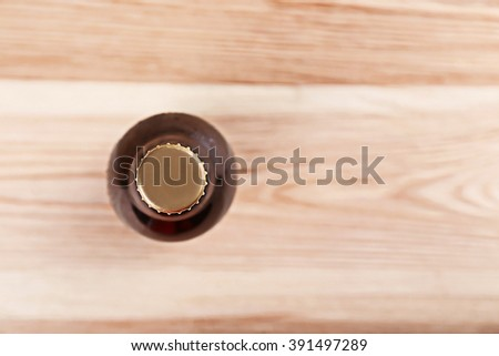 Beer bottle on wooden table - stock photo