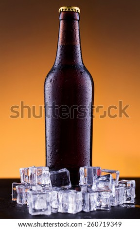 Beer bottle with water drops on ice in golden background. - stock photo