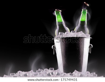 Beer bottles in ice bucket isolated on black - stock photo