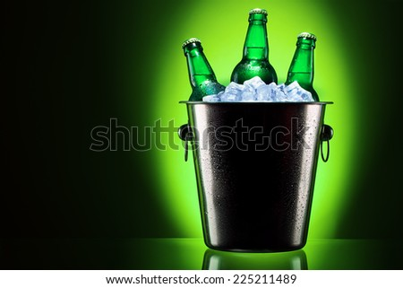 Beer bottles in ice bucket isolated on colored background - stock photo