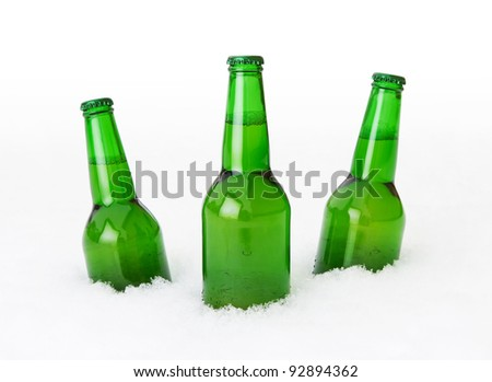Beer bottles in the snow over white background - stock photo