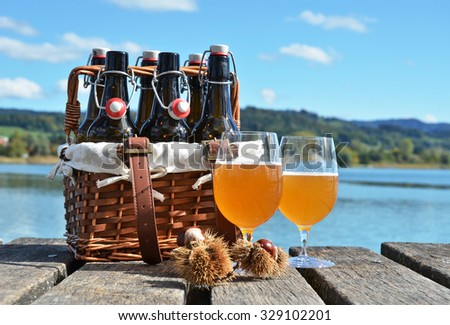 Beer bottles in the vintage basket on a wooden pier - stock photo