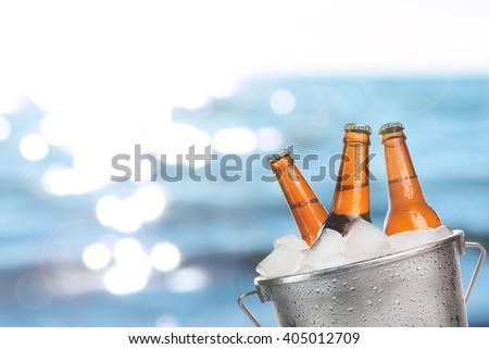 Beer bottles of cold fresh beer in ice bucket, on sea or ocean background - stock photo