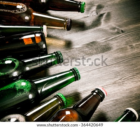 Beer bottles on a wooden table . Dark beer - stock photo