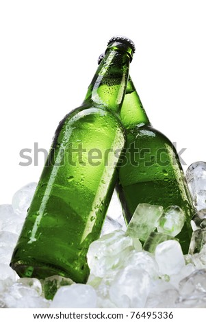 Beer bottles on ice cubes over white background - stock photo