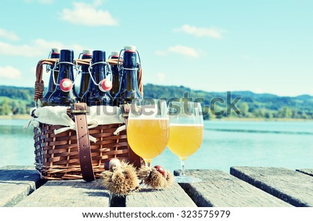 Beer bottles on the wooden pier against a lake - stock photo